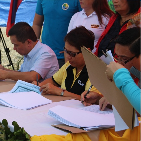 URBAN POOR HOUSING. Barangay Ilang head Arnolfo Ricardo Cabling, left, leads signing ceremonies for the P72 million urban poor housing project in Barangay Ilang on a P54 million 3-hectare lot donated by Holcim Philippines.